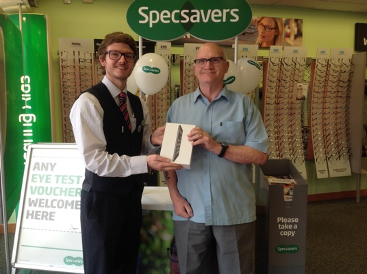 Sam Best, assistant store manager, with iPad winner John Cordin
