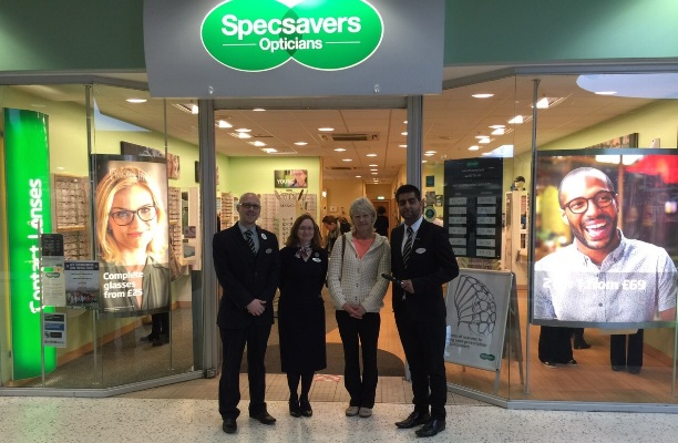 The Telford Specsavers staff outside the store with customer Janet Powell